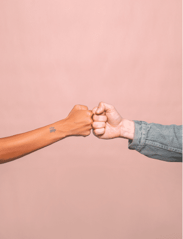 A woman and a man fist bump on a pink background