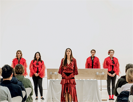 Five women in red clothes stand in front of a coffin on a white background with a crowd in front of them