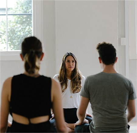 A man and woman attend a meditation class held by an asian woman in a white space with trees outside